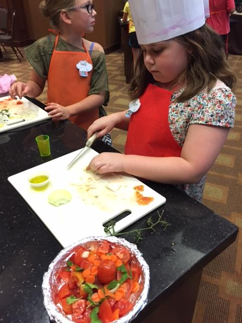 young girl cutting vegetables at a children's cooking class