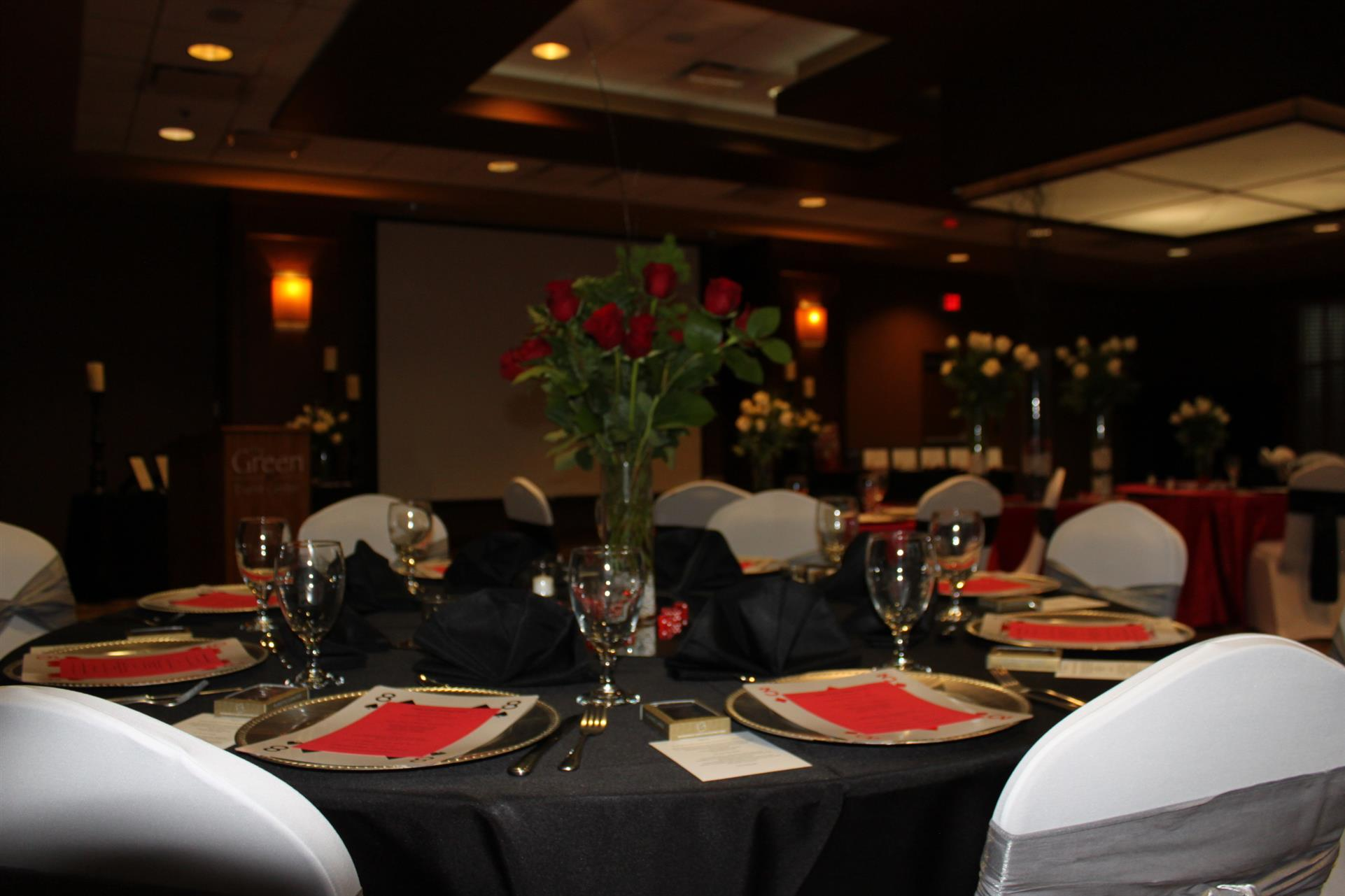 event space set for casino themed party with flowers and feather centerpieces