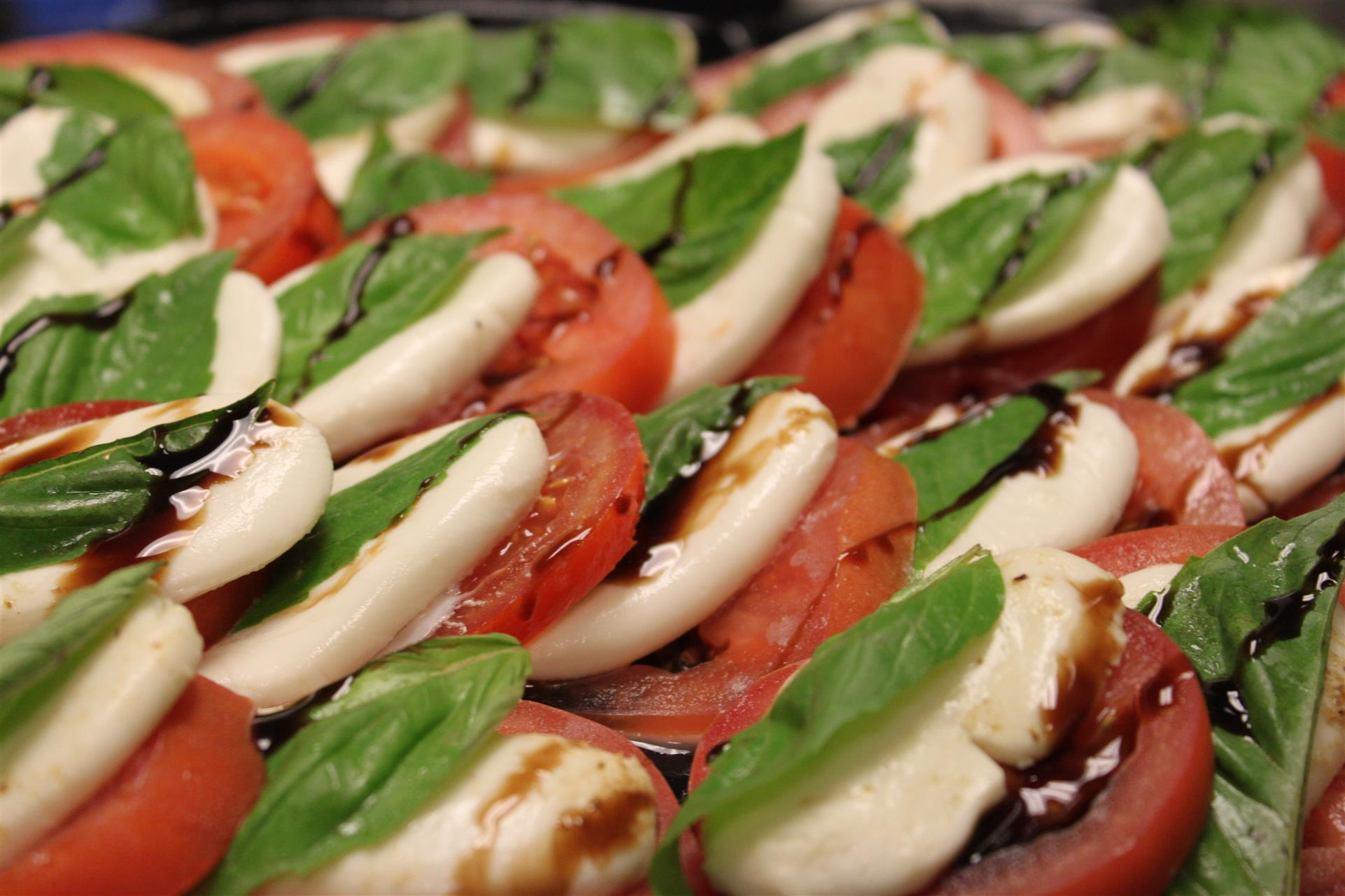 tray of sliced tomatoes, mozzarella cheese, and basil with balsamic drizzle