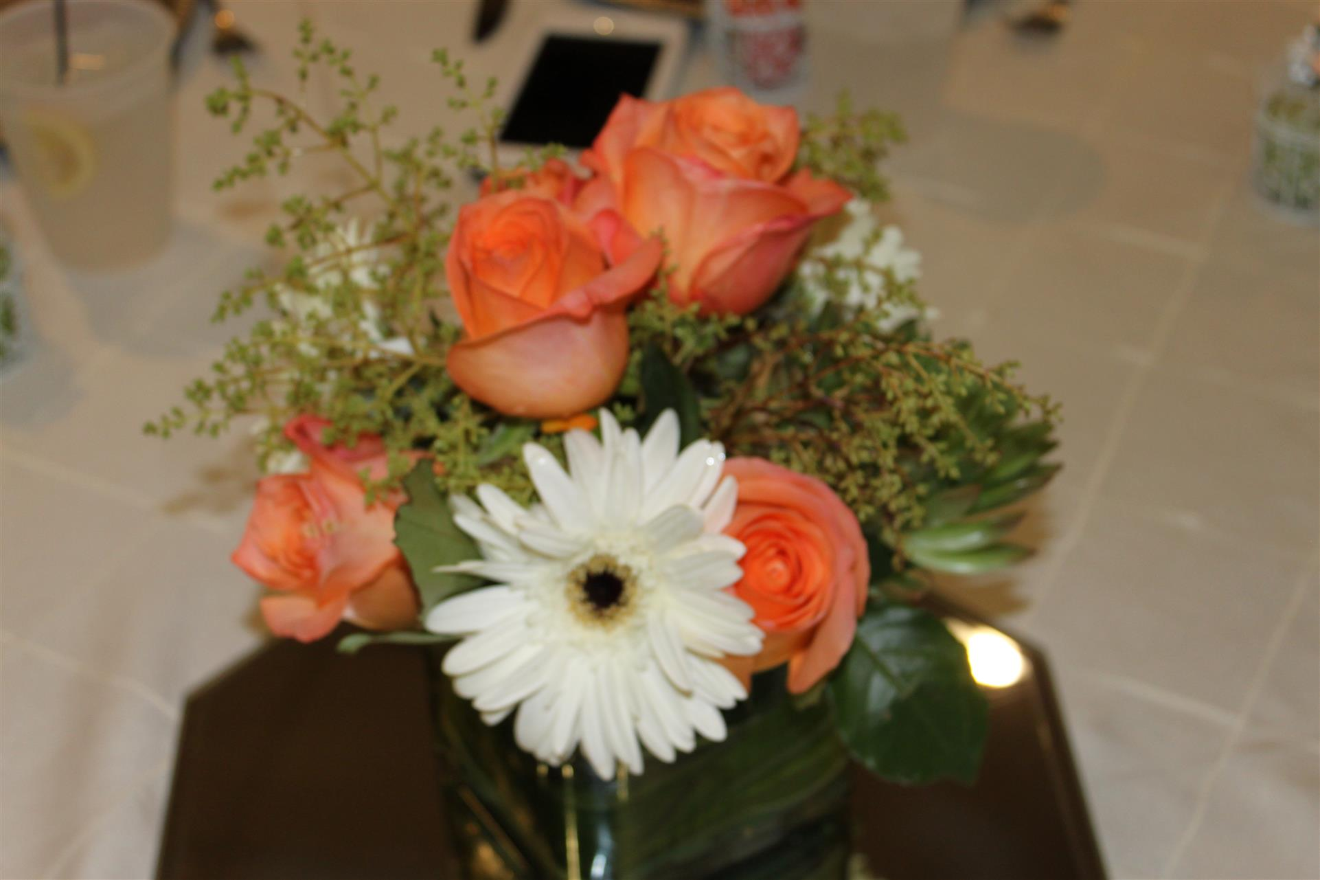 floral arrangement for a centerpiece with roses and daisies
