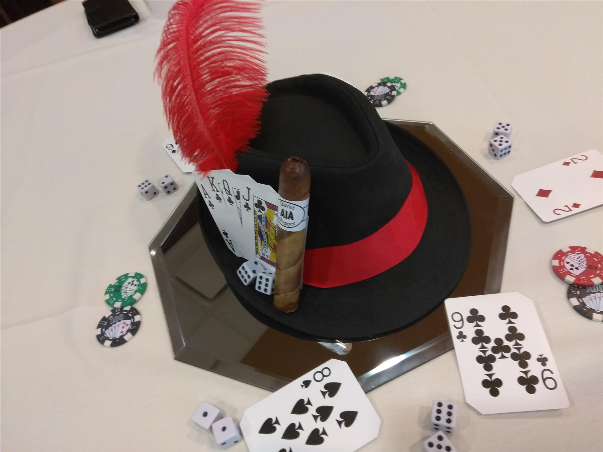 top hat for casino party with cigar, cards, poker chips, and dice