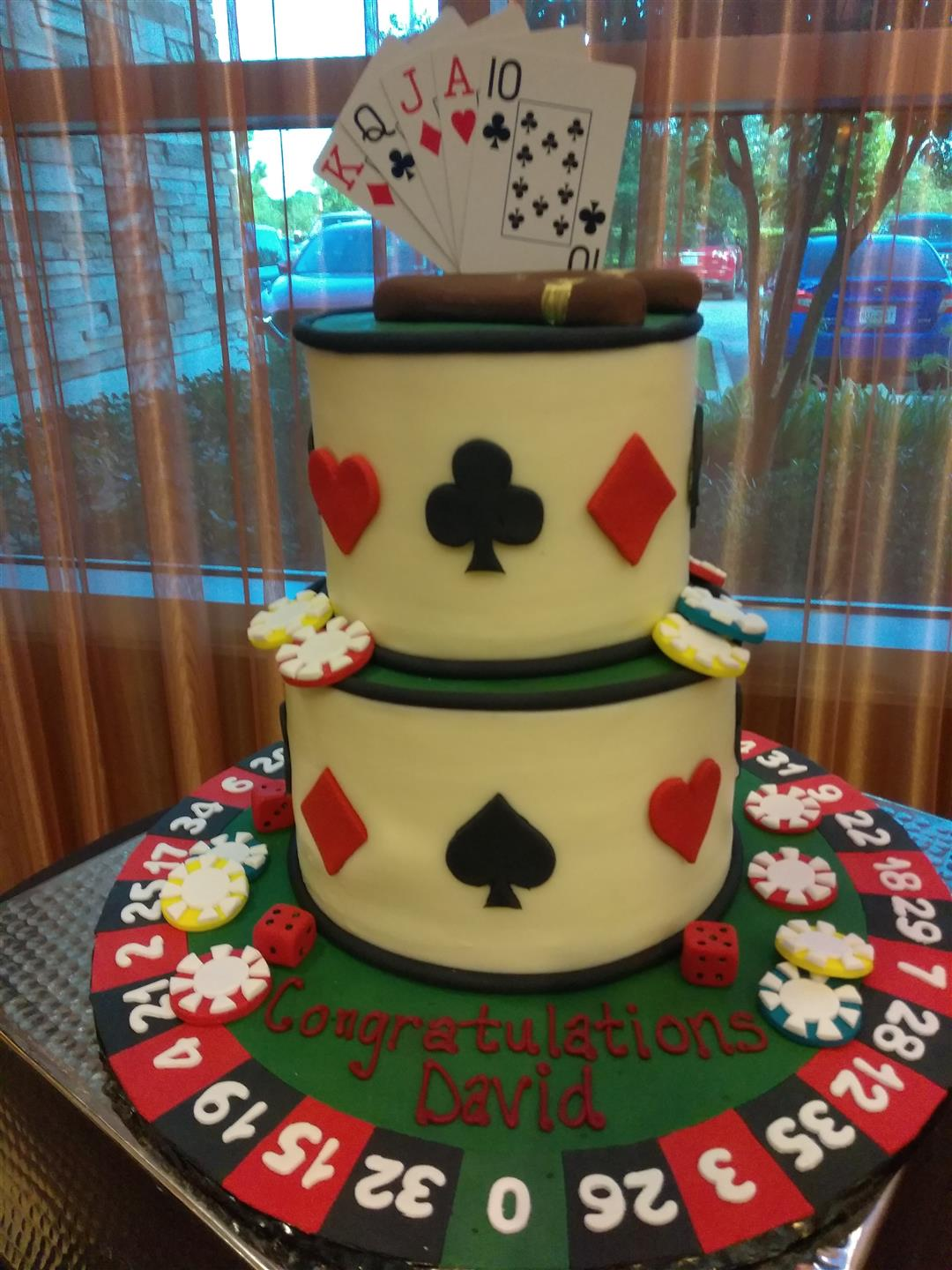 cake decorated for a casino party with cards, cigars, poker chips, and dice