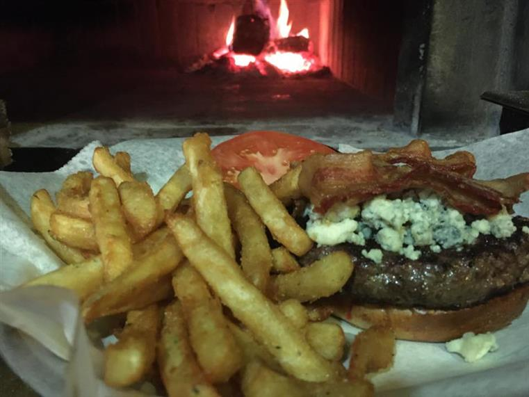 burger topped with bacon and bleu cheese crumbles. french fries on the side,