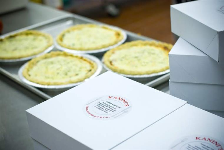 tray of baked quiches with Kanini's boxes