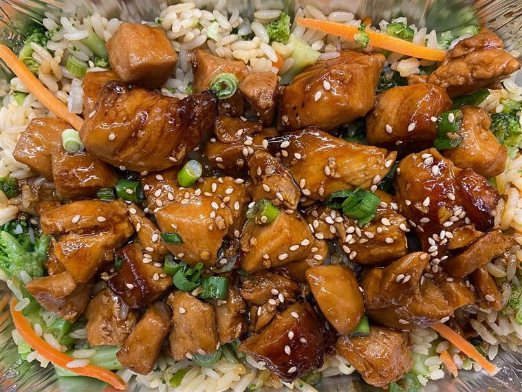 orange chicken over fried rice topped with sesame seeds and scallions