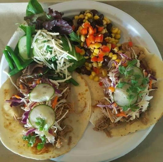tacos with pulled pork, cucumbers, cabbage slaw, and cilantro served with fresh green salad and cheese and a bean, corn salad