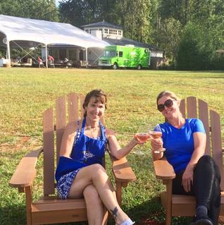 keely and her partner outside sitting in chairs having a toast with glasses of wine