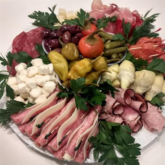 tray with various meats, cheeses, olives, peppers and pickles garnished with parsley