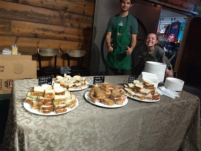 staff members at an event with a table filled with various sandwiches