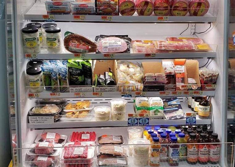 Refrigerated items on a shelf, which in includes bottles smoothies, kombucha drinks, packaged meats, cheeses, condiments, and cheeses