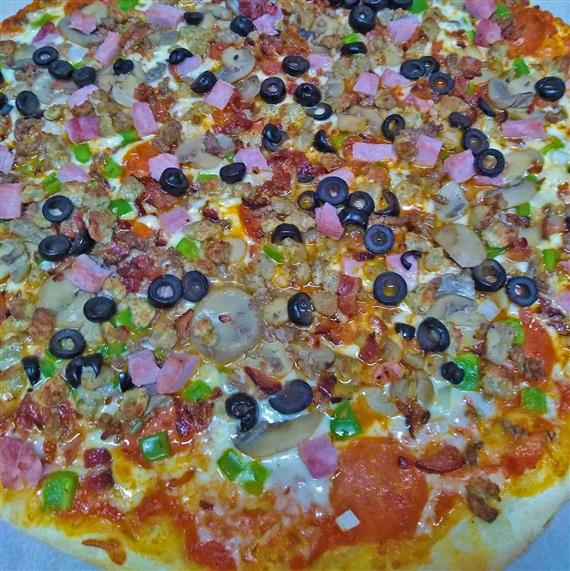 A pizza pie topped with olives, ham, peppers, mushrooms, pepperoni, and mozzarella cheese