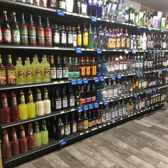 Shelves filled with various liquors and cocktail mixers