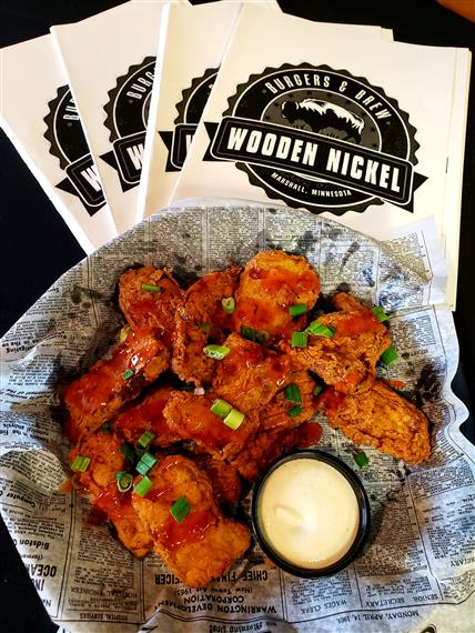 basket of boneless buffalo wings in a basket with a side of ranch, stack of Wooden Nickel napkins