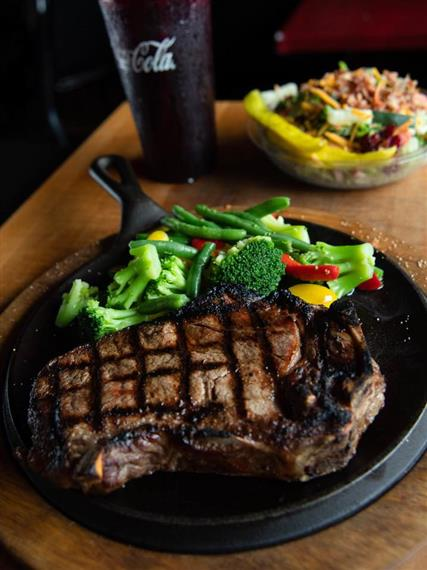 Grilled ribeye steak with mixed veggies and a side salad