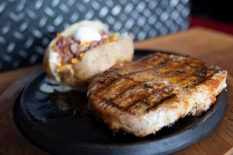grilled pork chop with a baked potato