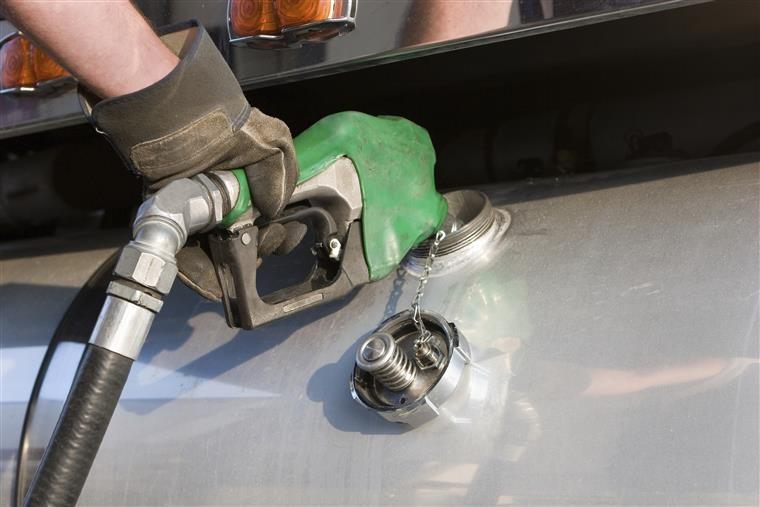 hand filling up the gas tank on a truck.