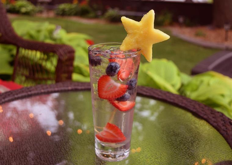 A berry vodka soda with fresh berries and a pineapple garnish