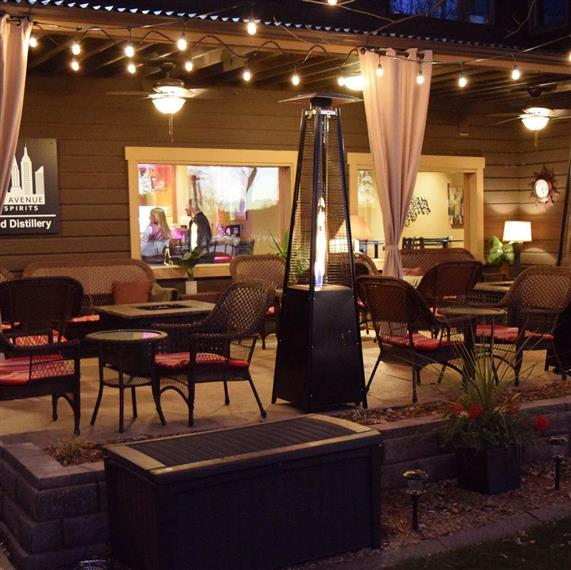 Outdoor patio with tables and chairs, rope lights, and fire pits