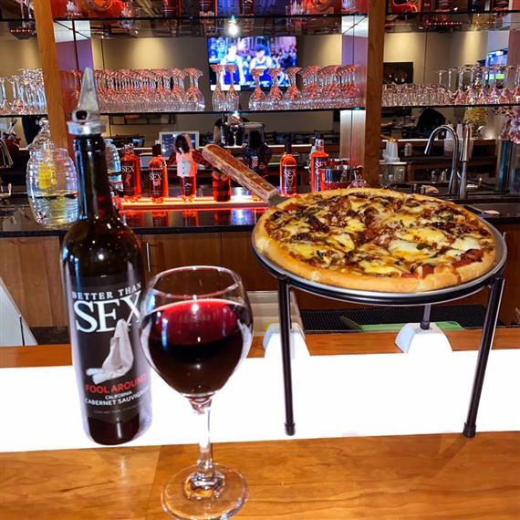 "A bottle of ""Better Than Sex"" wine with a full glass and a personal pizza"
