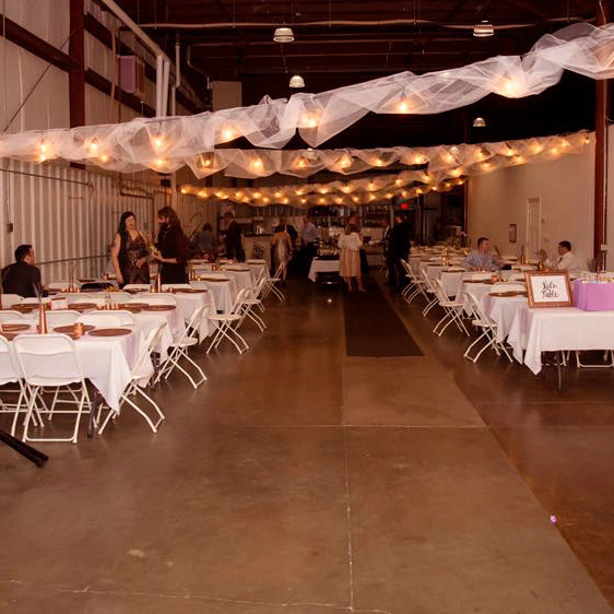 A catered event with rope lights and set rows of tables with linens