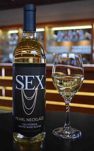 "A bottle of ""Better Tahn Sex"" Peal necklace california white wine blend accompanied by a glass filled with the wine"