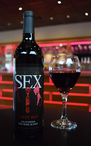 "A bottle of ""Better Tahn Sex"" Three Way California Red Wine Blend accompanied by a glass filled with the wine"