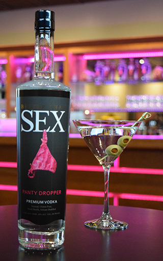 "a bottle of the ""panty Dropper"" premium vodka next to a martini on the bar"