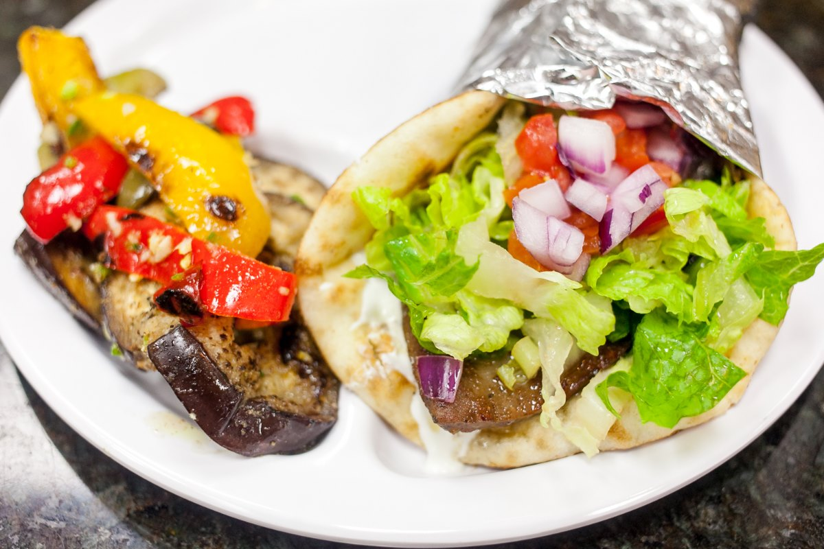 A gyro in pita topped with onion, tomato, feta and roasted vegetables on the side