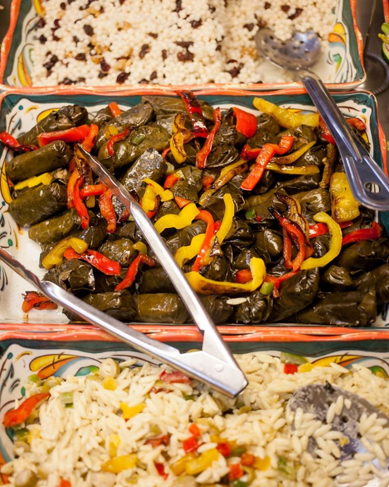 A tray filled with grape leaves, rice and beans