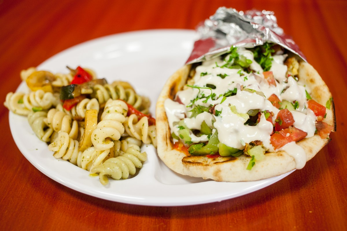 A gyro with a side of pasta salad