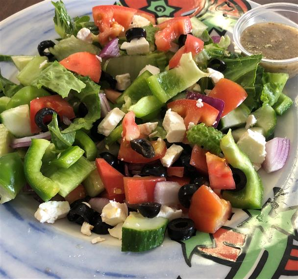 greek salad with cucumbers, olives, tomatoes, feta cheese, peppers, red onions and lettuce served with balsamic