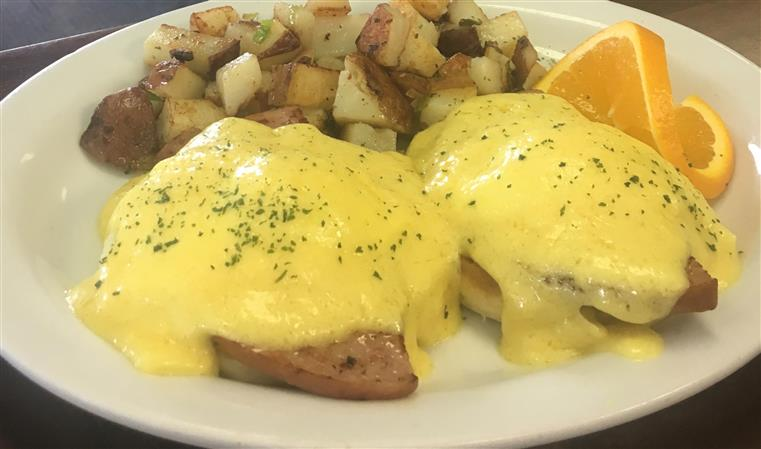 eggs benedict with homefries and an orange