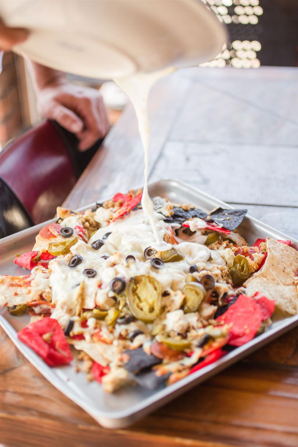 extra cheese being poured onto nachos with chips, jalapenos, olives and cheese