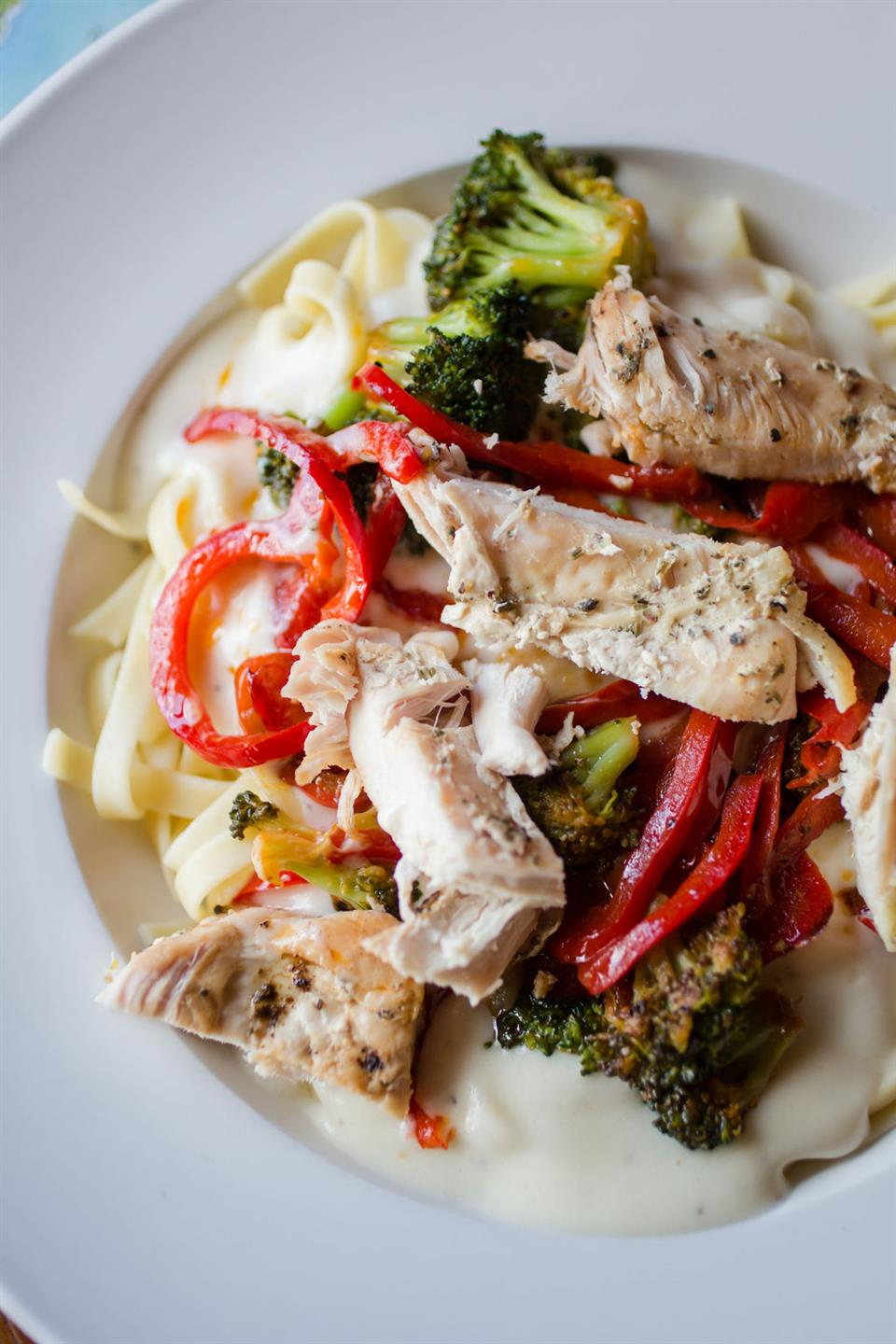 pasta with cream sauce, grilled chicken, peppers, broccoli and parmesan cheese