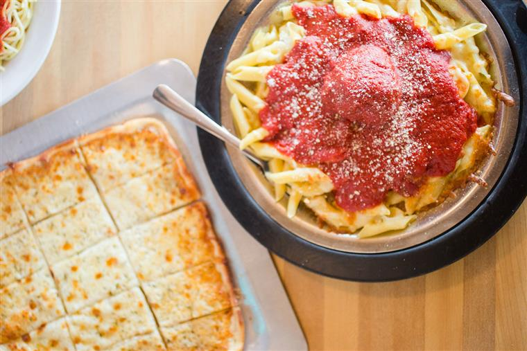 pasta with red sauce and a flatbread on the side