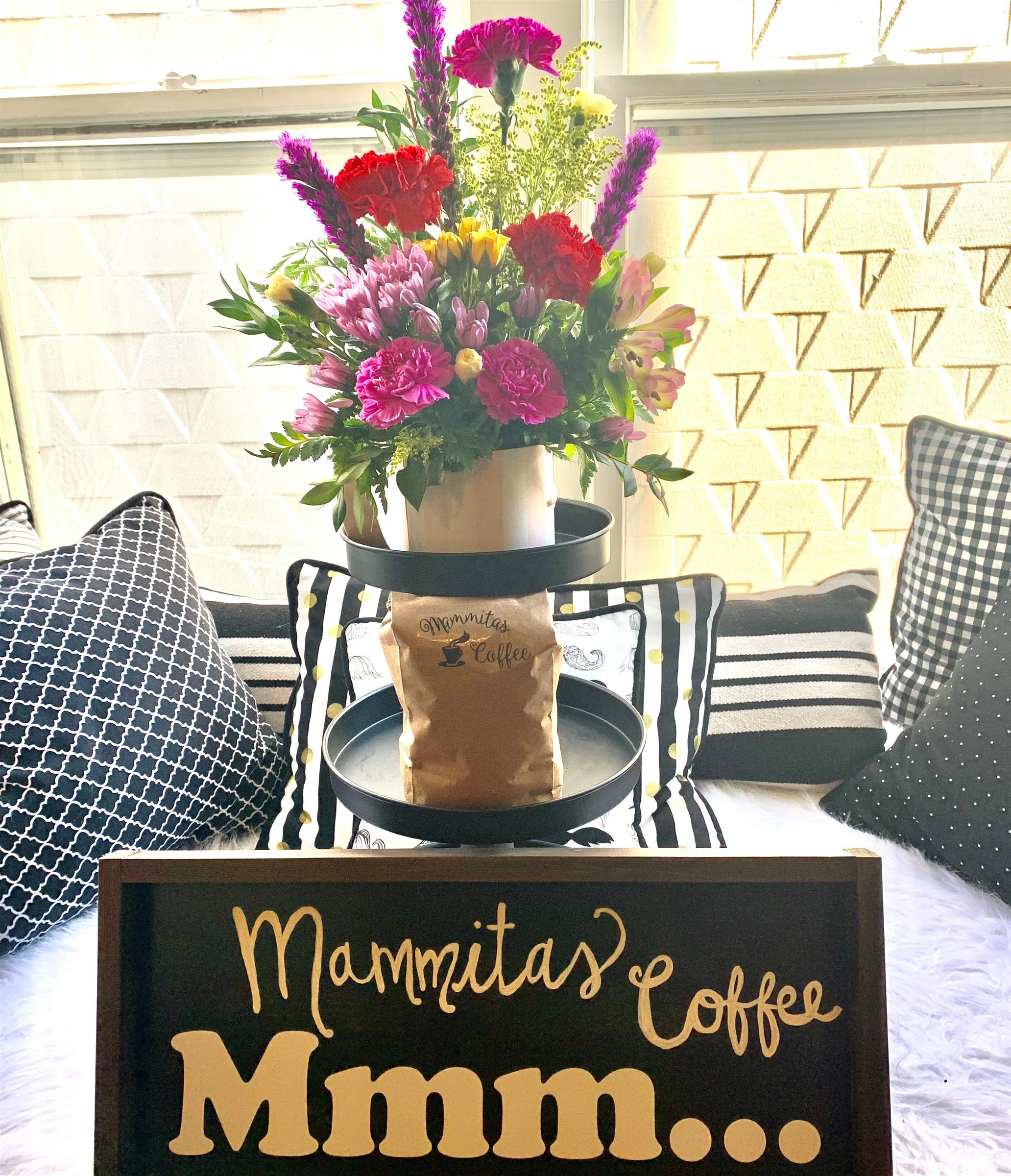 bouquet of fresh flowers on table behind Mammitas Coffee Sign