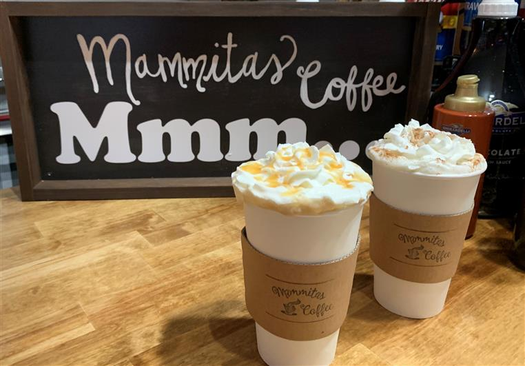 two lattes with whipped cream on countertop with Mammitas Coffee sign