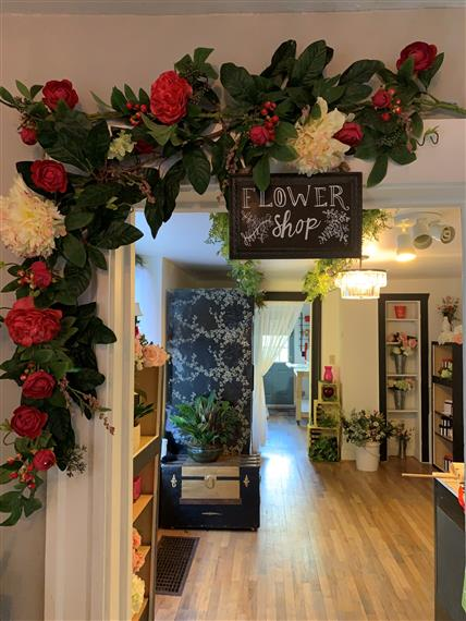 """Lobby of Flowers by Jacqueline with rose archway and """"Flower Shop"""" sign"""