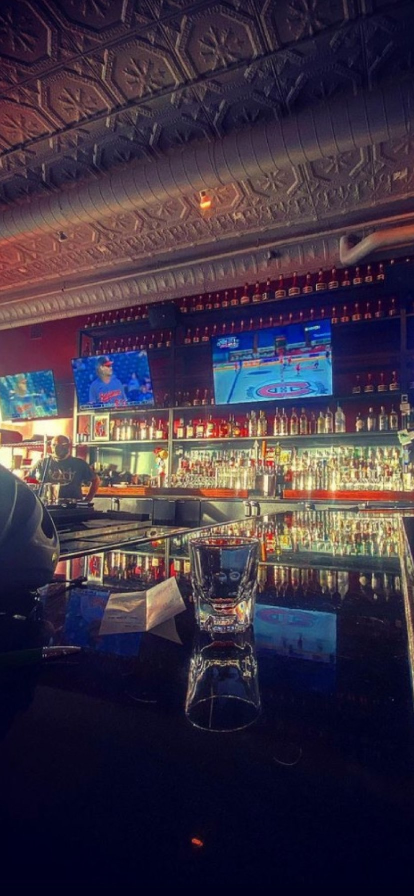 glass on bar counter with bartender and sports game on televisions