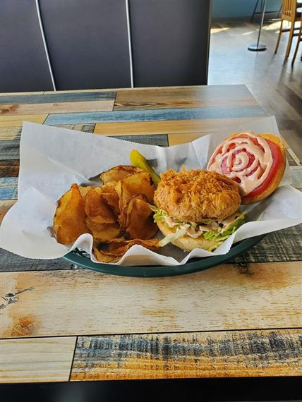 crispy fish sandiwhc on a bun with chipotle mayo, coleslaw, and tomato, side of fries