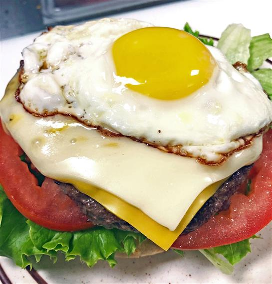 burger topped with lettuce, tomatoes, cheese and an egg