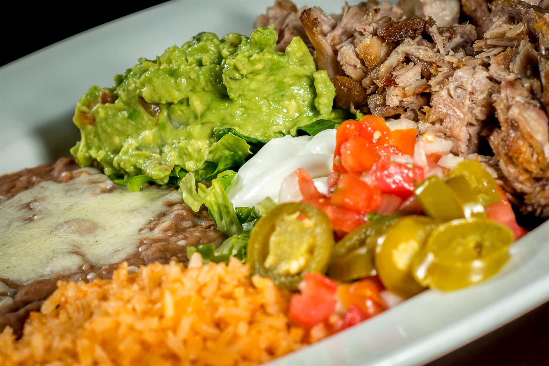 Carnitas Platillo: Traditional Mexican style deep-fried pork. Served with guacamole and sour cream.