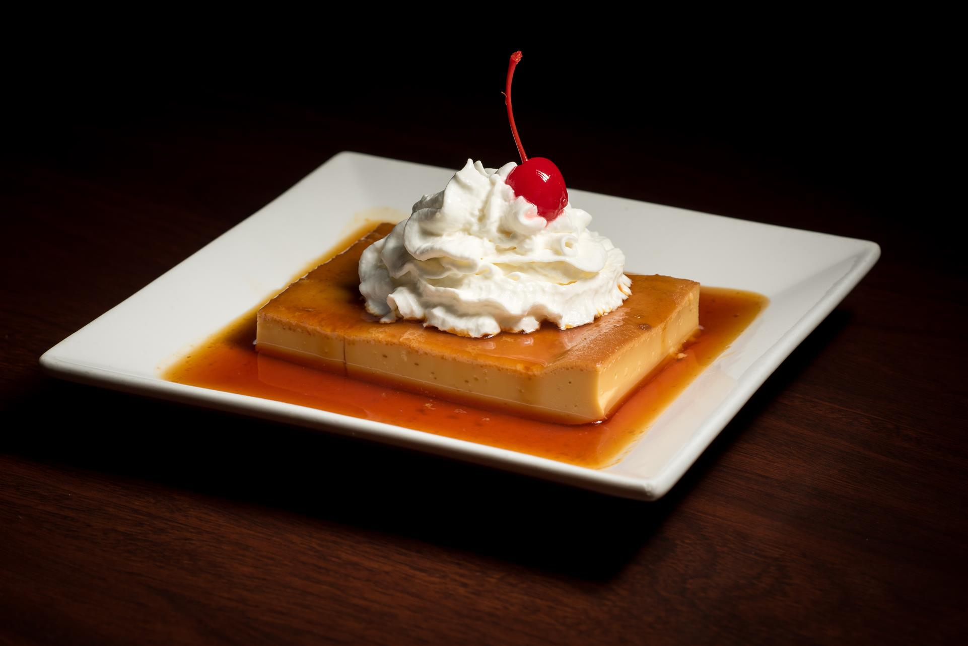 Flan dessert topped with whipped cream