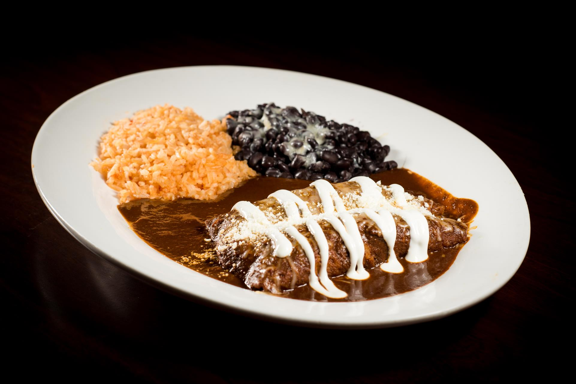 Enchiladas de Mole: Two tortillas rolled and filled with chicken, covered with homemade mole, cheese, onions and sour cream