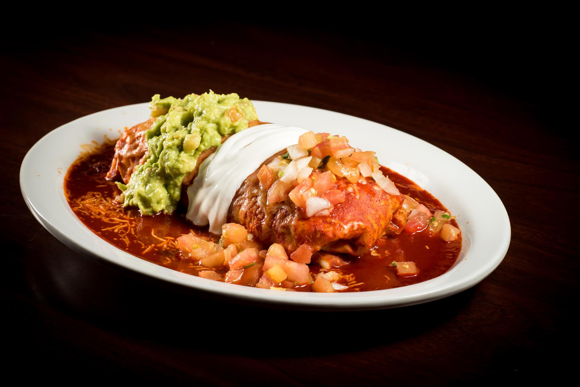Wet Burrito: meat, whole beans and rice. Topped with our homemade enchilada sauce, cheese, sour cream and guacamole.