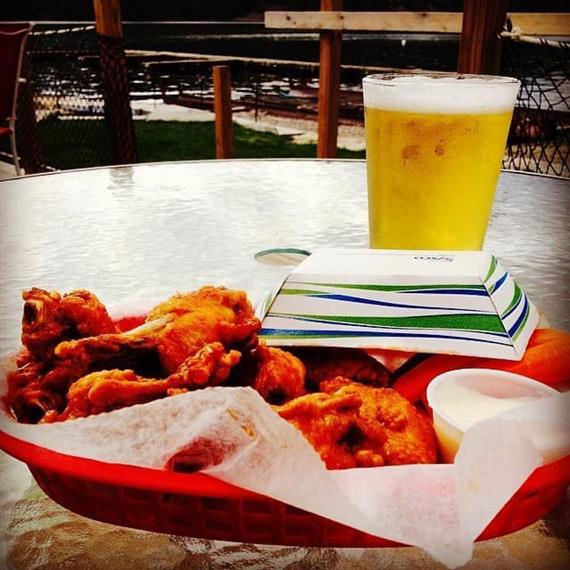 basket of buffalo wings with side of ranch and carrots, glass of beer on table