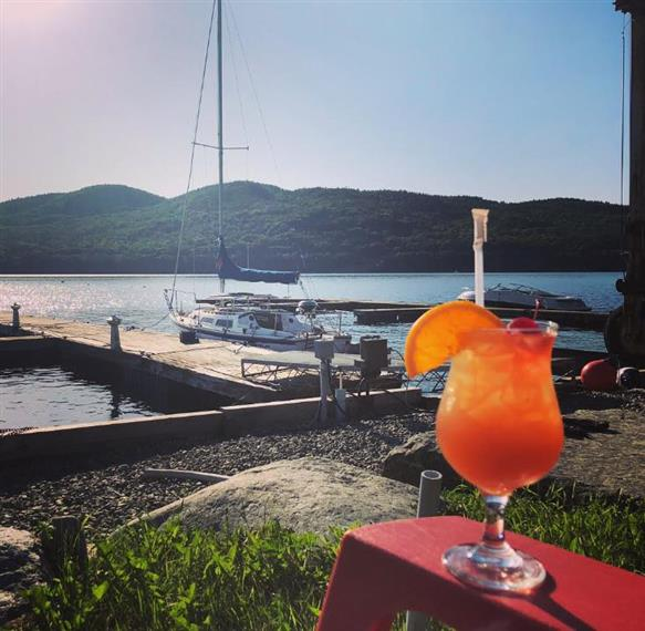 fruity cocktail on the arm of a lawn chair overlooking boats and Lake Champlain
