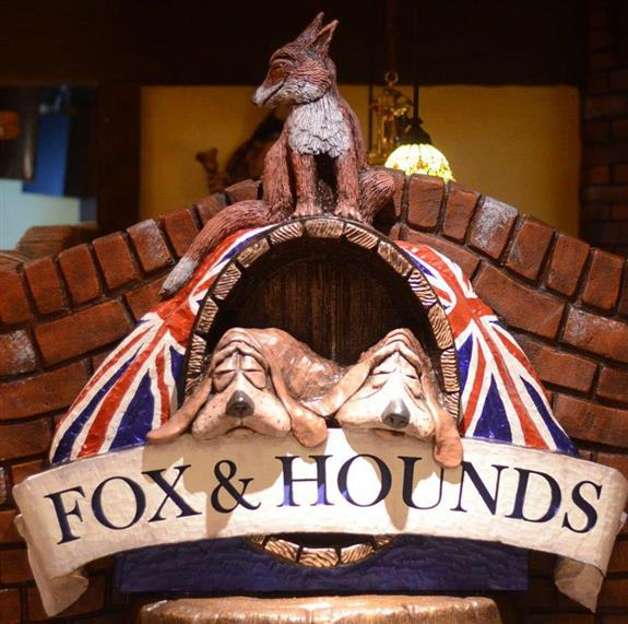 a small brick wall with two ceramic dogs and a ceramic fox on top. titled: fox & hounds
