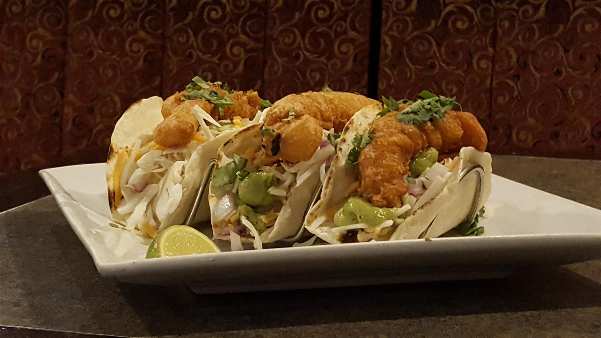 three fish tacos with fried fish with guacamole and lime