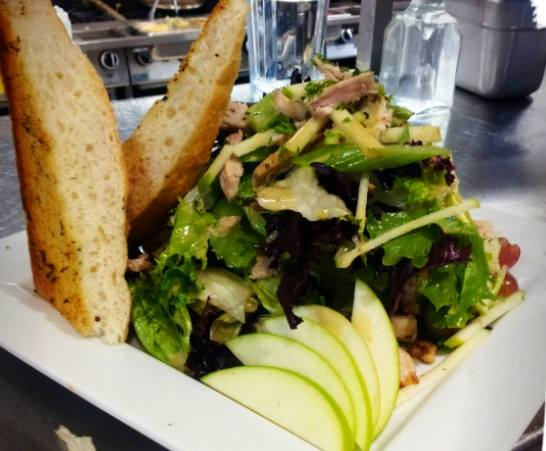 a salad with lettuce onions and green apples. two pieces of bread